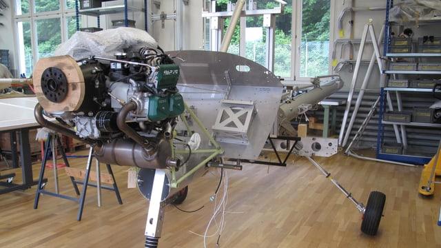 Motor und Fahrgestell eines Kleinzflugzeuges, das in einer Werkhalle zusammen gebaut wird.