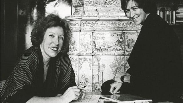 Zwei Frauen, eine am Tisch sitzend, die andere seitlich auf dem Tisch sitzend, beide lachend in die Kamera schauend.