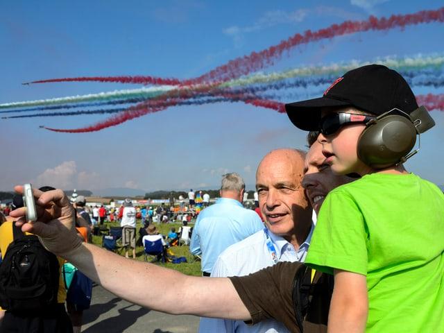 Bundesrat Ueli Maurer lässt sich von einem Mann mit Kind vor aufregender Kulisse fotografieren.