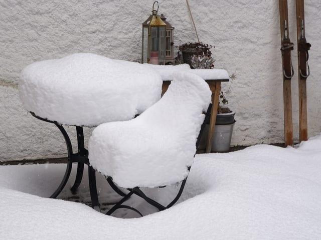 Gartenstuhl und Bank mit knapp 20 cm Schnee bedeckt.