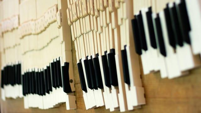 Einzelne Tasten eines Klaviers auf einem Tisch ausgelegt.