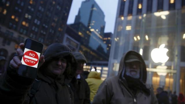 Demonstrants cun iPhones davant in Apple Store en ils Stadis Unids.