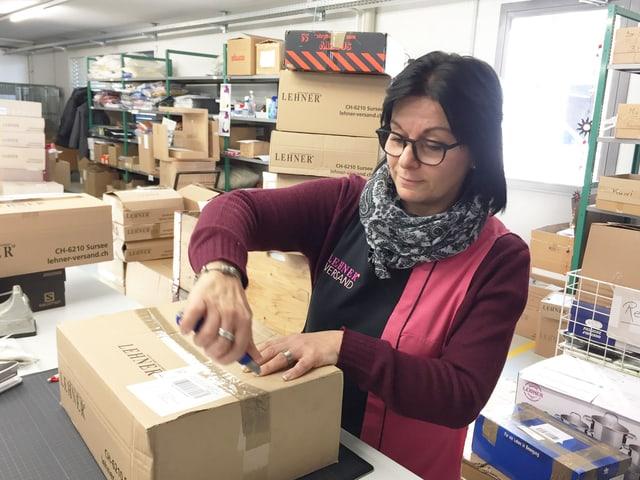 Frau macht Paket auf