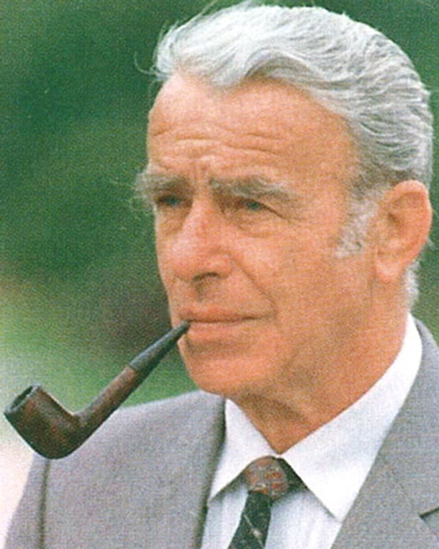 Der grauhaarige Mann raucht Pfeife.