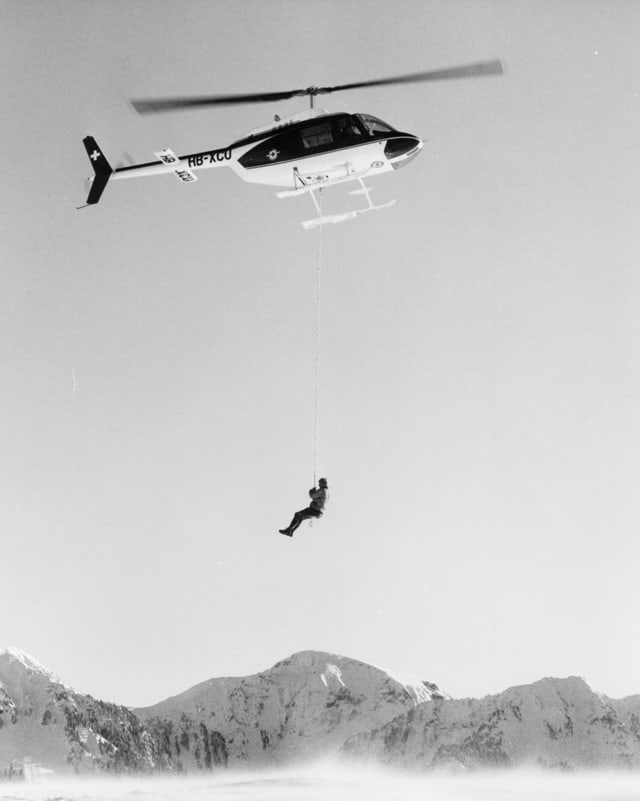 Ein Mensch hängt an einem Seil an einem Helikopter.