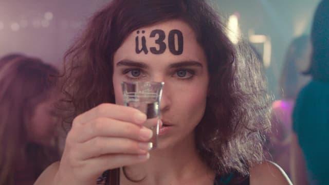 """Eine Frau hat ein auf der Stirn """"ü30"""" geschrieben und hält ein Glas Schnaps in der Hand."""