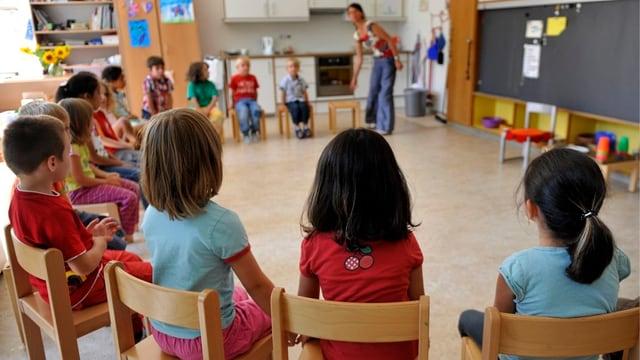 Kinder sitzen im Kindergarten im Kreis