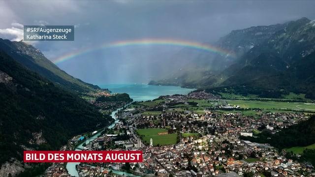 Regenbogen spannt sich über Tal mit See