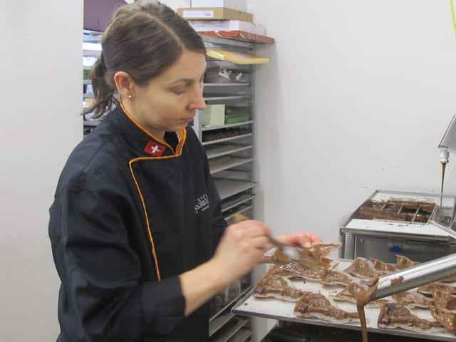 Eine Confisseurin verteilt mit einem Pinsel die Schokolade in den Plastikformen.