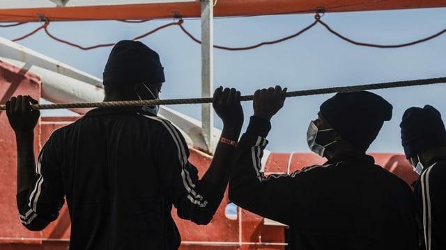 Zwei afrikanische Männer von hinten auf einem Schiff.