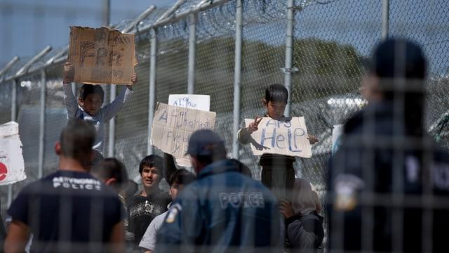 Flüchtlinge vor einem Stacheldrahtzaun halten Transparente mit der Aufschrift, «Helft uns», in die Höhe. Im Vordergrund Polizisten von hinten.