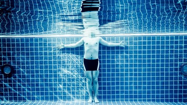 Eine Person steht in einem Schwimmbad.