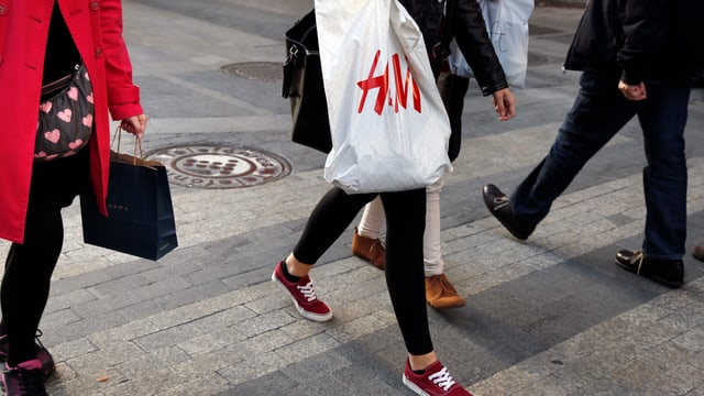 Eine Frau trägt eine Einkaufstüte von H&M durch eine Fussgängerzone.