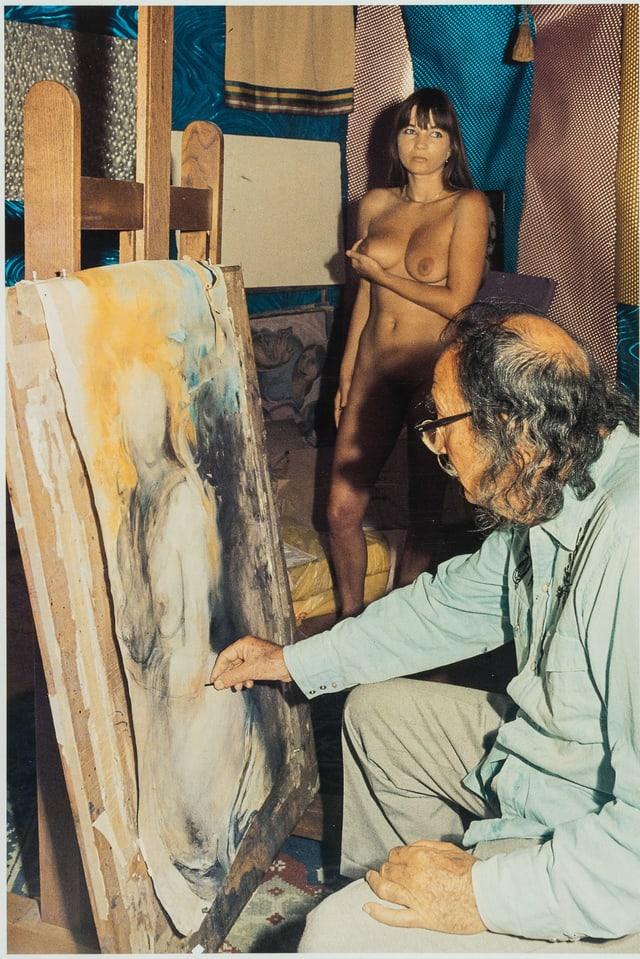 Ein Mann mit schütterem, grauen, lockigen Haar, Brille und Schnauz malt einen Akt. Im Hintergrund eine junge, nackte Frau, die ihre rechte Brust anhebt.