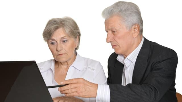 Ältere Mann erklärt Frau am Computer