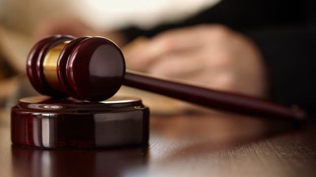 Gerichtshammer, im Hintergrund unscharf Hände