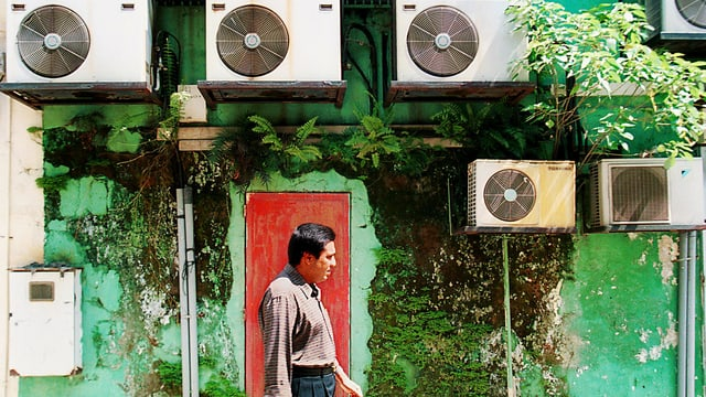 Ein Mann läuft an einer Häuserfassade mit Klimanlagen vorbei