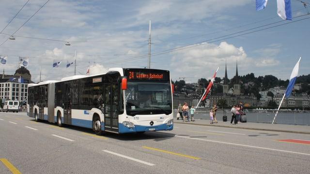 Ein blauweisser Bus, welcher auf einer Strasse fährt.