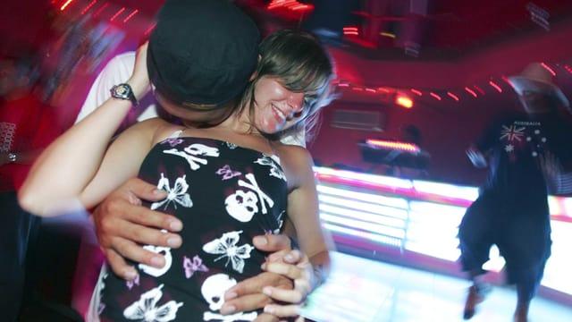 Ein junges Paar tanzt auf der Tanzfläche einer Disko.