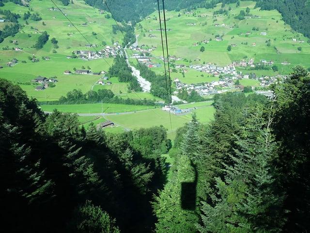 Der Schatten einer Gondelbahn ist im Wald zu sehen, dahinter liegt das Tal.