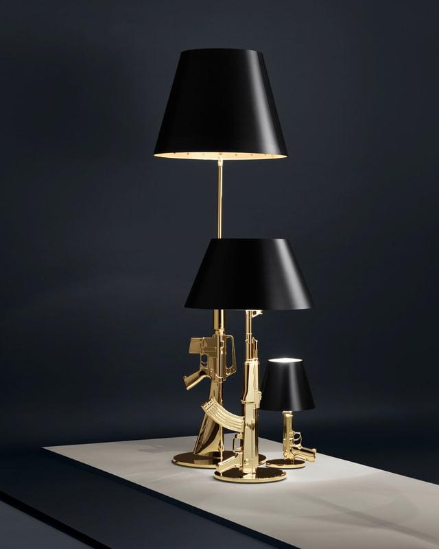 Drei Lampen mit goldenen Ständern in Form von Waffen.