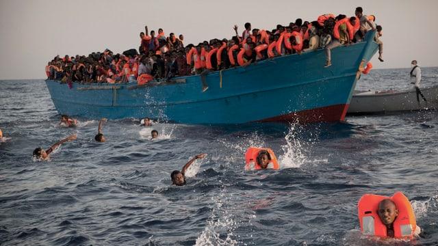 Überfülltes, blaues Boot, etliche Menschen befinden sich mit Schwimmwesten im Wasser.