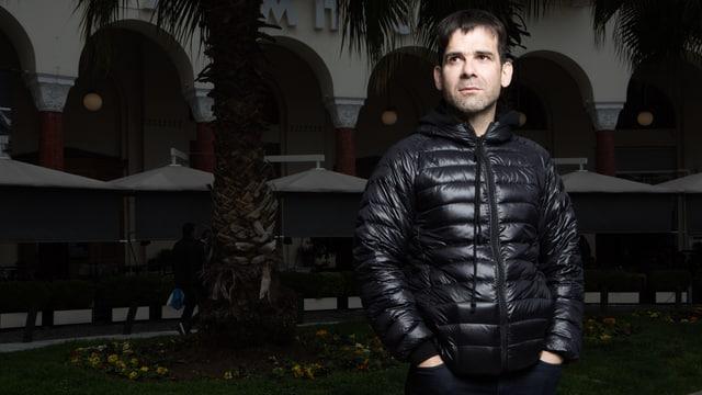 Menelaos Karamaghiolis trägt eine schwarze Jacke.