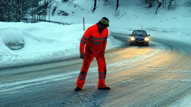 Mann in oranger Kleidung auf vereister Strasse.