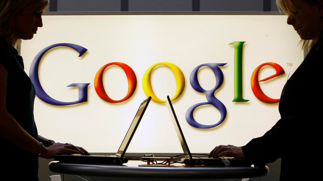 Zwei Frauen arbeiten stehend an ihren Notebooks vor einem Google-Logo.
