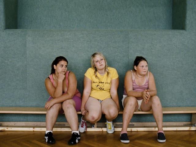 Drei Mädchen auf einer Turnbank