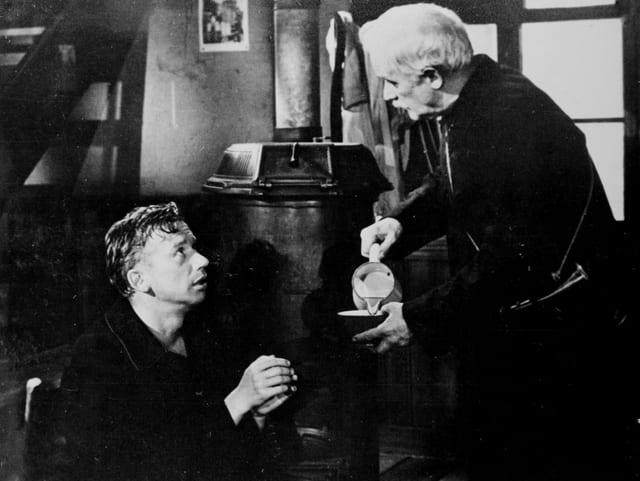 Zwei Männer in einem Wohnzimmer. Der jüngere sitzt und schaut zum älteren mit Schnauz auf. Dieser schenkt ihm eine Tasse Milch ein.