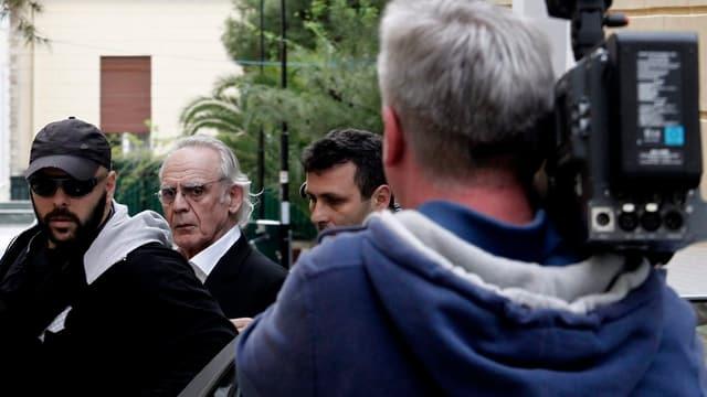 Akis Tsohatzopoulos wird abgeführt - im Vordergrund ein Kameramann, der das Ganze filmt, von hinten.
