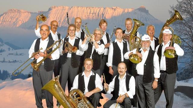 Die 13 Musikanten der BoueleMusig mit ihren Instrumenten vor einer Schnee bedeckten Bergkulisse im Abendrot.