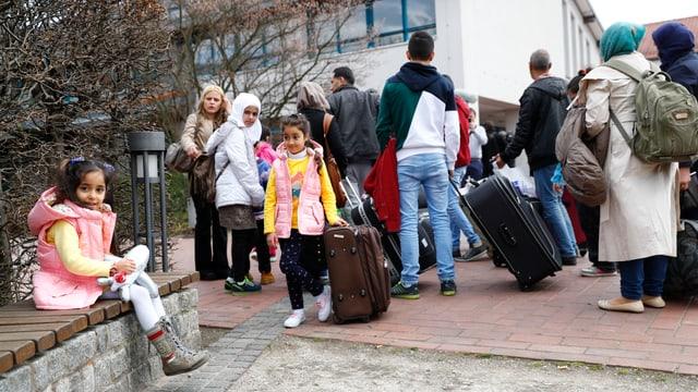 Migranten mit Koffern vor einem grossen Gebäude in Deutschland.