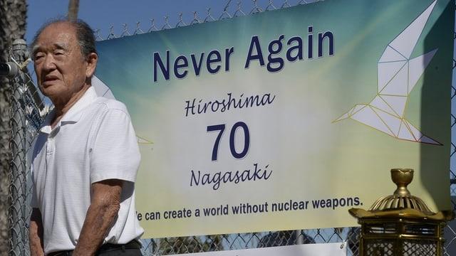 in um giapunais avant in placat cun scrit «Never again»
