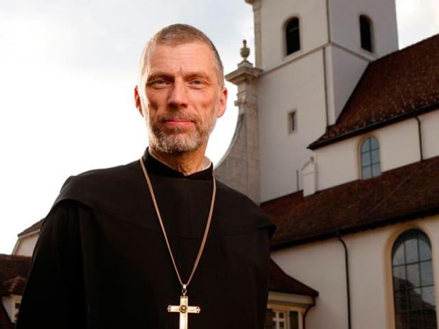 Bild halbnah eines Mannes in schwarzer Mönchskutte mit umgehängtem Kreuz, draussen vor dem Kloster stehend.