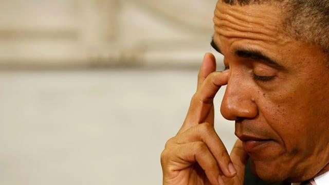 US-Präsident Barack Obama reibt sich mit dem Finger das Auge.
