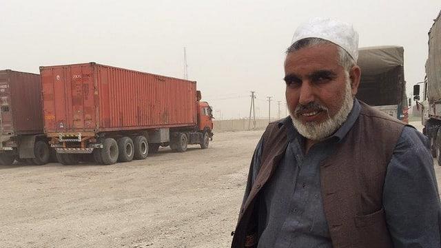 Gulab Jan vor parkierten Lastwagen.