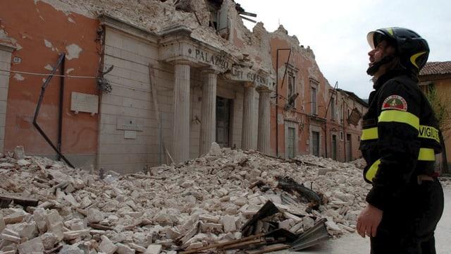 Feuerwehrmann blickt auf zerstörten Palazzo nach Beben in L'Aquila (Bild aus dem Jahr 2009).