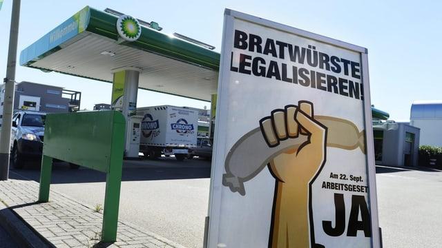 Tankstelle mit Poster, auf dem «Bratwürste legalisieren» steht.