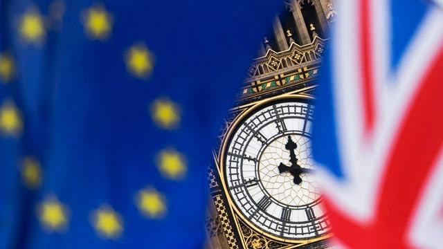 Purtret d'ina bandiera da l'UE ed ina da la Gronda Britannia davant il Big Ben a Londra.