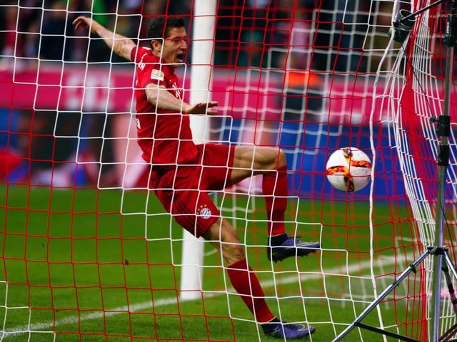 Robert Lewandowski von Bayern München schiesst den Ball ins Netz.