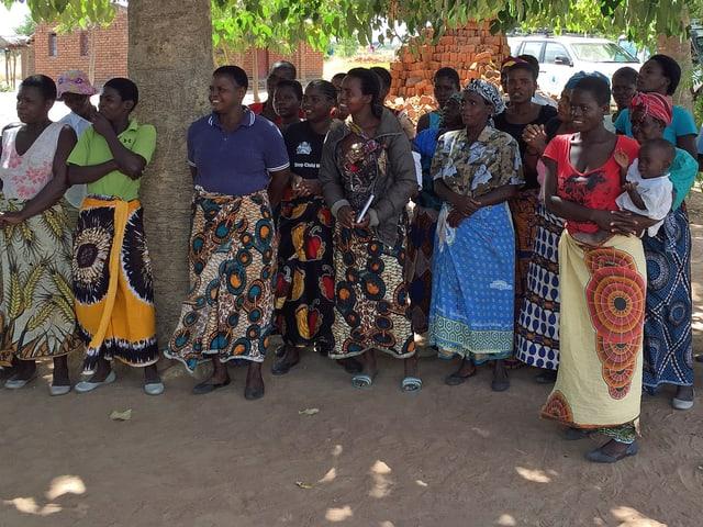 Frauen stehen auf dem Dorfplatz unter einem Baum in einer Reihe