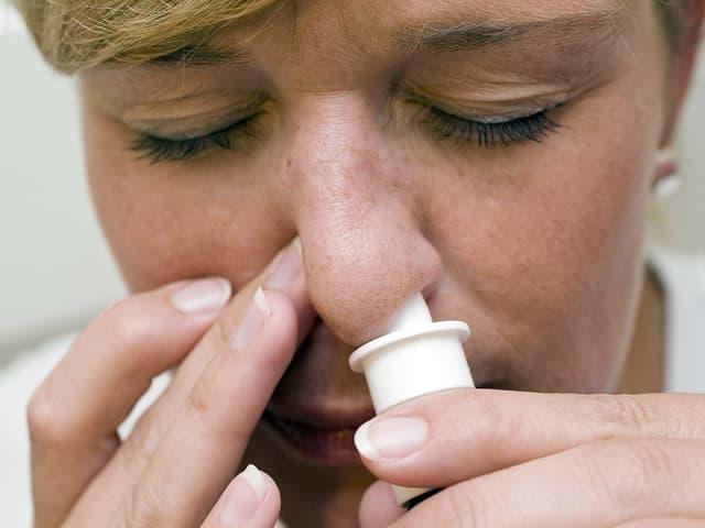 Frau nutzt Nasenspray