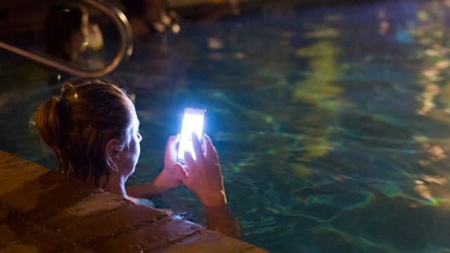 Frau mit Handy in Pool