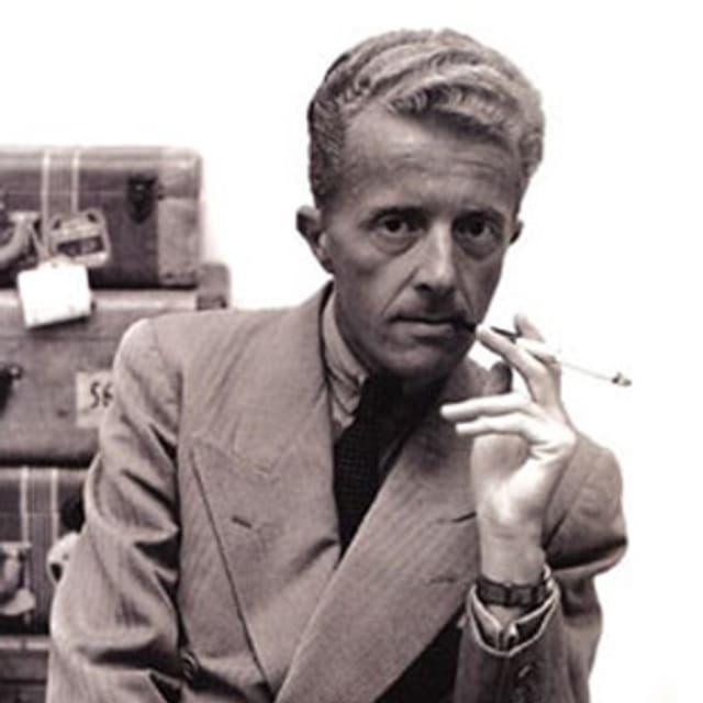 Schwarz-weiss Portrait des Schriftstellers Paul Bowles, der mit einer Zigarette in der Hand vor einem Stapel Koffern sitzt.