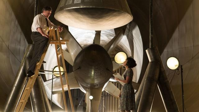 Kazimierz und Mary sprechen miteinander. Kazimierz steht auf einer Leiter unter einer Rakete.