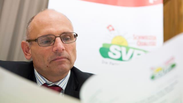 Kopf eines Mannes zwischen SVP-Plakaten