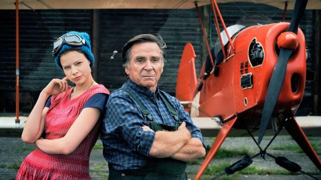 Ein junges Mädchen und ein Mann stehen vor einem alten Doppeldecker-Flugzeug.