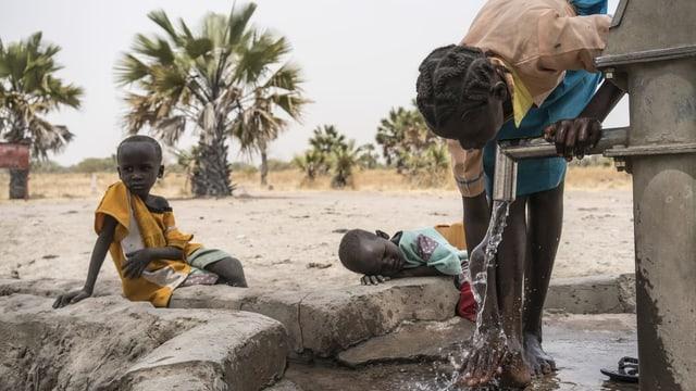 Uffants nairs en il Sudan che baivan aua dad ina funtauna nova.